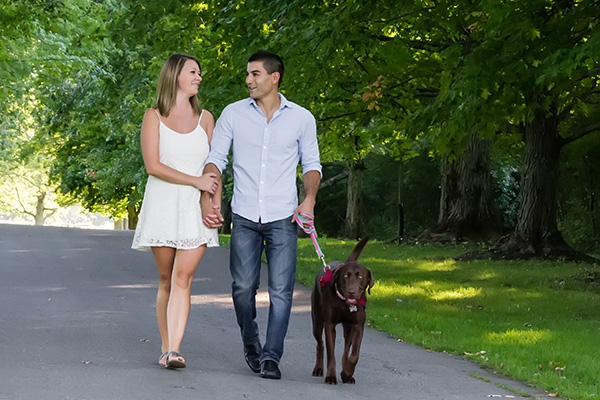 Couple walking down the street with a dog in East Aurora, NY