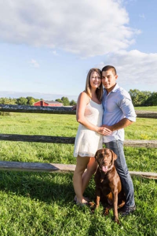 Engaged couple in the country with a dog.