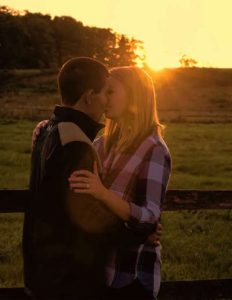 Engaged couple in the country by a fence taken by Fallesen Photography LLC