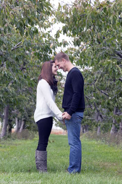 Engaged couple in a field with trees located in Niagara County, NY
